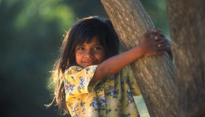 Young girl dressed in yellow grabbing a tree trunk