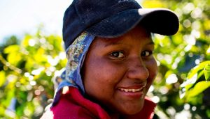 Woman farmer with denin cap smiling at the camera on a sunny day