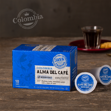 Box of 10 count of Colombia Alma Del Café coffee on a wooden table with glass of coffee