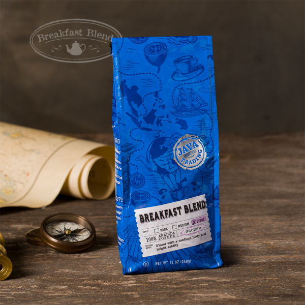 Bag of 12 ounce of Breakfast Blend coffee on a wooden table with rolled map and compass