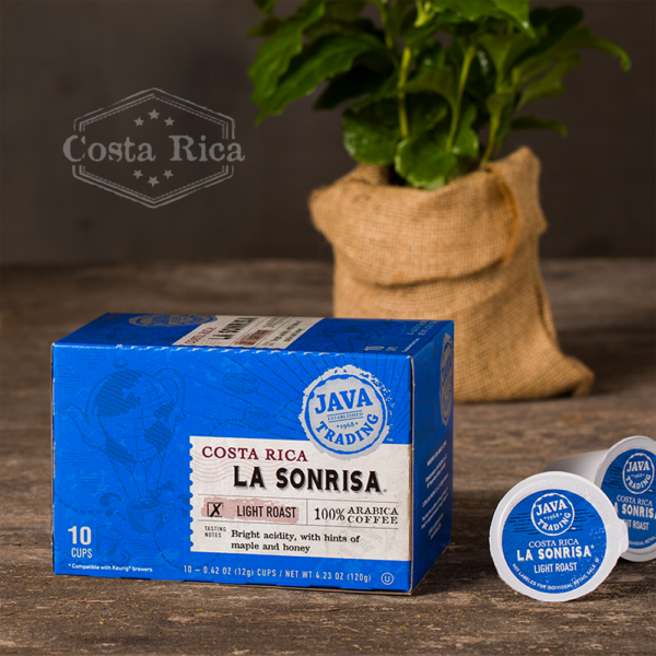 Box of 10 count of Costa Rica La Sonrisa coffee on a wooden table with coffee plant in burlap bag