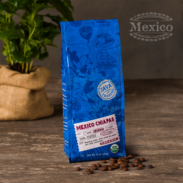 Bag of 10 ounce of Organic Mexico Chiapas coffee on a wooden table with coffee plant in burlap bag