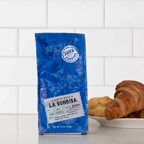 Bag of 12 ounce Costa Rica La Sonrisa coffee on a kitchen counter with a plate of croissants