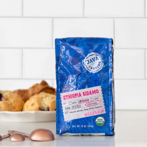 Bag of 10 ounce Organic Ethiopia Sidamo on a kitchen counter with a plate of scones