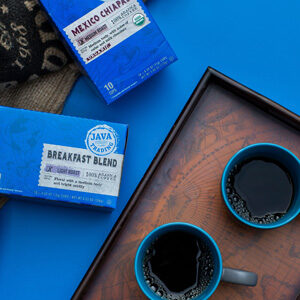 Two single-serve boxes of Java Trading coffee, wooden tray and two mugs full of coffee