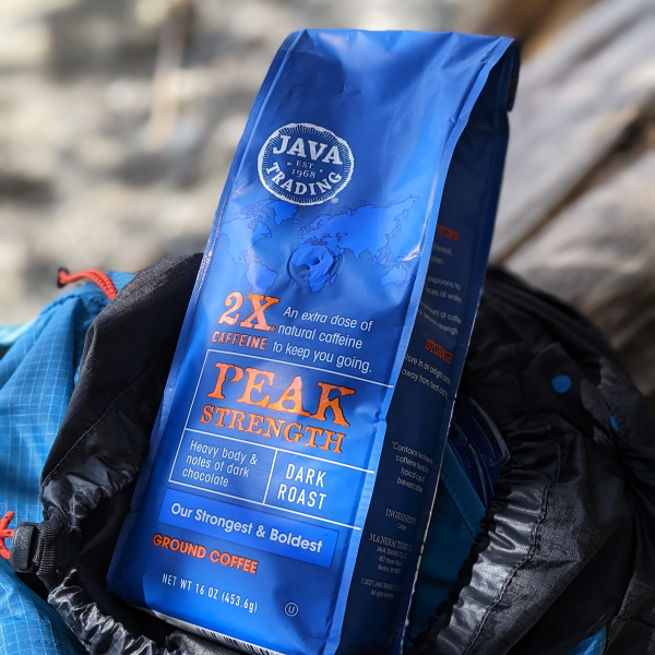 Bag of Java Trading Peak Strenght High Caffeine 16 ounces ground coffee, sitting top of a blue backpack.